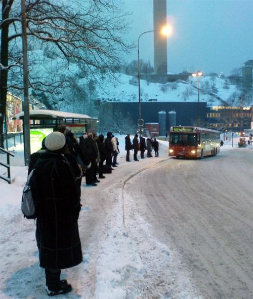 Folk väntar på Nacka-Värmdö-bussarna i Henriksdal på vintern