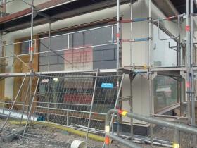 Byggställningar framför Puls & Träning i Henriksdalshamnen