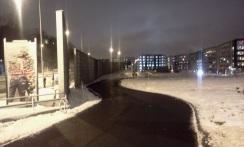 asfalterad gång- och cykelväg intill Kanalvägen i Henriksdalshamnen med plank mot värmdövägen