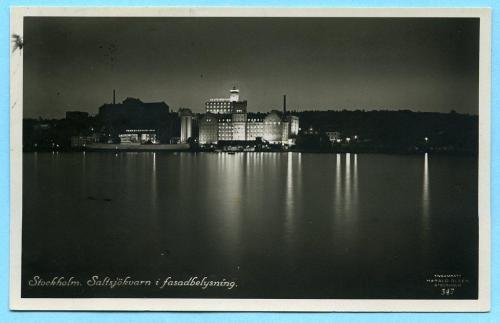 Vy- och reklamkort av Harald Olsen visar Saltsjöqvarns fasadbelysning, 1930-talet